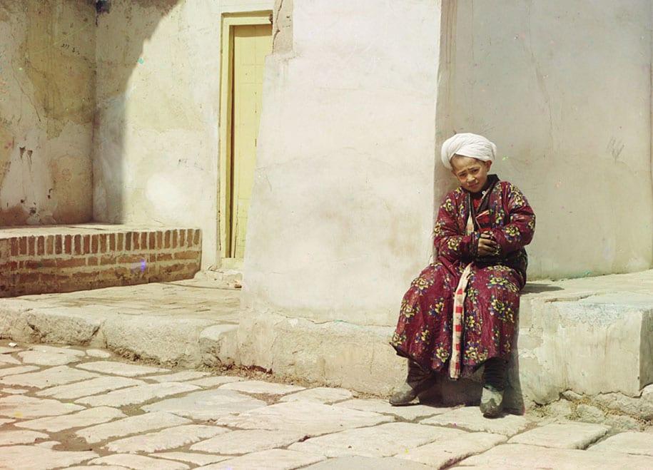 Menino sentado na mesquita em Samarkand